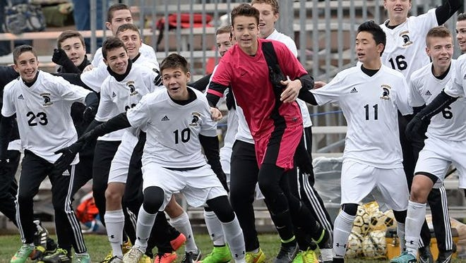 Greece Athena gets ready to celebrate its Class A boys soccer state championship win on Saturday in Middletown.