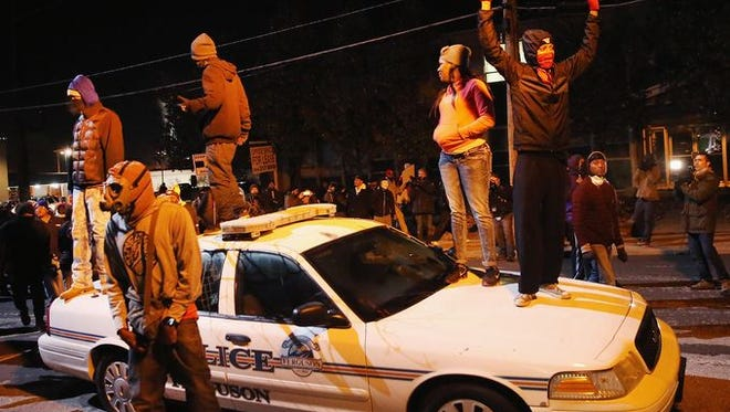 FERGUSON, MO - NOVEMBER 25: A police squad car is damaged by demonstrators during a protest on November 25, 2014 in Ferguson, Missouri.