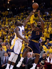 Cleveland Cavaliers forward LeBron James (23) shoots the ball over Golden State Warriors forward Draymond Green (23) during the second quarter in game one of the NBA Finals at Oracle Arena.