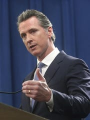 California Gov. Gavin Newsom discusses the lawsuit the state will likely file against President Donald Trump over his emergency declaration to fund a wall on the U.S.-Mexico border Friday, Feb. 15, 2019, in Sacramento, Calif.