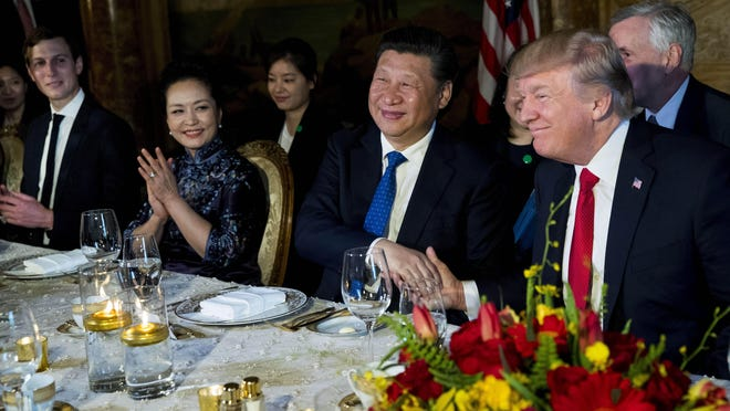 President Donald Trump and President Xi Jinping of China shake hands during a dinner at Mar-a-Lago on April, 6, 2017. At left are Jared Kushner, Trump's son-in-law, and Peng Liyuan, Xi's wife. [DOUG MILLS/The New York Times)