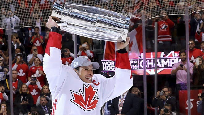 In this Sept. 29, 2016 file photo, Canada's Sidney Crosby hoists the trophy following his team's victory over Europe in the World Cup of Hockey finals, in Toronto. The closest comparison to the NHL's summer restart is the 2016 World Cup of Hockey. Following a lengthy, unscheduled break because of a pandemic, teams have just two weeks of camp at home before traveling to Toronto or Edmonton for one exhibition game ahead of real competition.