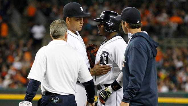 Detroit Tigers Miguel Cabrera stops Rajai Davis to say something to him as head trainer Kevin Rand, left, and manager Brad Ausmus lead Davis off the field after he was hurt running out a ground out to end the second inning against the Minnesota Twins on Saturday.