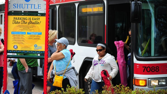 Festivalgoers exit the shuttle to begin their day at Festival International de Louisiane in downtown Lafayette, La., Sunday, April 28, 2013.