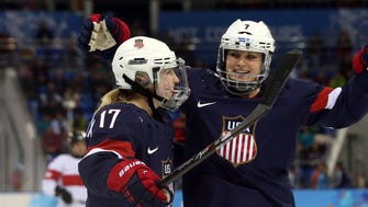 USA forward Monique Lamoureux-Morando (7) celebrates with forward Jocelyne Lamoureux-Davidson (17) after scoring a goal against Switzerland in a women's preliminary round game during the 2014 Sochi Olympics.