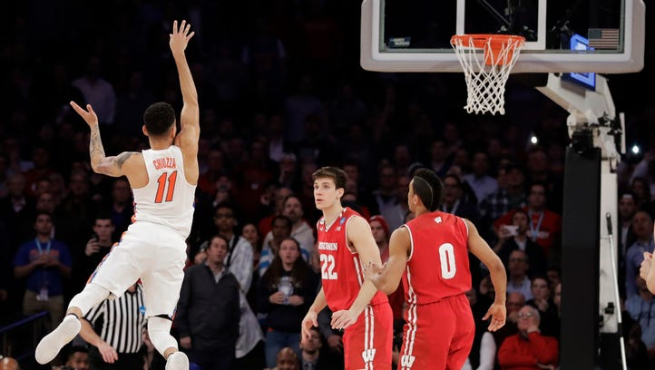 Florida guard Chris Chiozza (11) puts up a last second 3-point shot to score the game-winning points against Wisconsin in overtime of an East Regional semifinal game of the NCAA men's college basketball tournament.