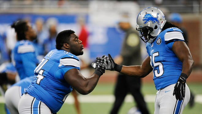 Lions right tackle Michael Ola, left, and running back Joique Bell shake hands on the field before the Oakland game at Ford Field.
