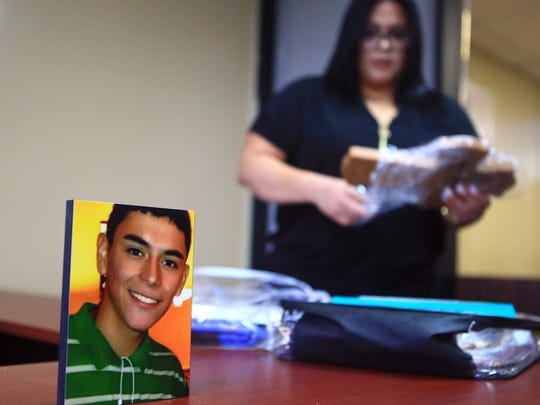 A photo of Josiah Christian Cantu is displayed as his mother Marina Garcia looks through other photos of him on April 11, 2017, in Corpus Christi. Cantu died from a gun shot wound in the stomach last year. Corpus Christi Police initially said Cantu shot himself, but a year later Nueces County District Attorney Mark Gonzalez is seeking a criminal indictment against a friend.