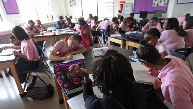 Seventh-grade students take notes in a science class at the Reach Academy for Girls.