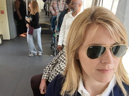 Detroit Free Press reporter Elisha Anderson rides the QLINE as she headed towards the DIA for her selfie as part of Free Press' Great Race in Detroit last month.