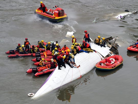Search and rescue team members work on a TransAsia Airways passenger plane that crashed into the Keelung River in Taipei, Taiwan, on Feb. 4.
