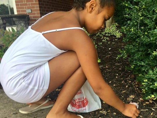 Dimonie Hemphill, 9, places a rock at Chambersburg Brethren in Christ Church the afternoon of July 24. Locals in the county are painting rocks and then placing them in different areas for people to find.