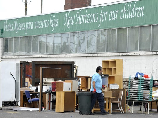 An unidentified worker sorts and throws out equipment behind the former Matrix Human Services Head Start business, which is in the back of the old Lincoln Brass Works building.