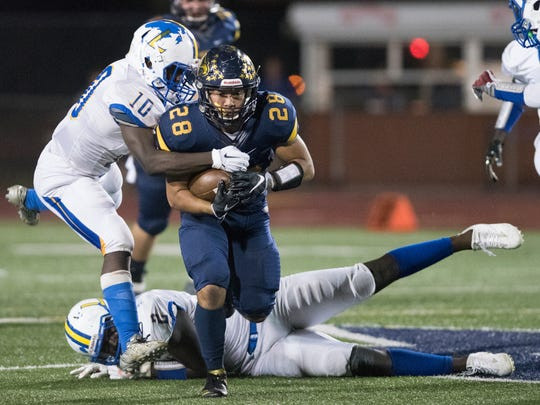 Elan Sommala of Naples fights off a Largo defender during the 6A regional semifinal game at Naples High Friday night, November 17, 2017.