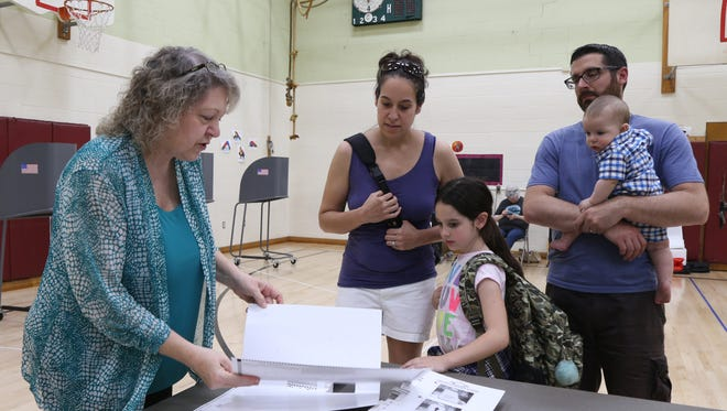 Poll worker, Nancy McCombs prepares ballots for, Aimee and Kurt Bressler with their children, Ariana and Kaden at the Arthur S. May School for Tuesday's school budget vote on May 15, 2018.