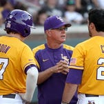 LSU head coach Paul Mainieri, center, discusses the game with Danny Zardon (27) and Chris Chinea (26) during the 11th inning of a game at Mississippi State earlier this season.
