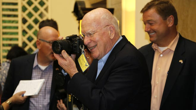 Sen. Patrick Leahy, D-Vt., turns his camera on reporters after a news conference Saturday in Havana, Cuba. Pictured at right is Sen. Dean Heller, R-Nev.