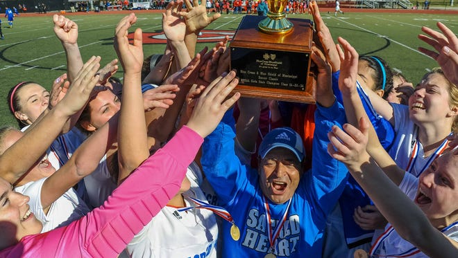 Sacred Heart coach Joe Falla Sr. and his players hoist the trophy following their 1-0 overtime win in the 1A/2A/3A Girls Soccer Championship held Saturday in Clinton.