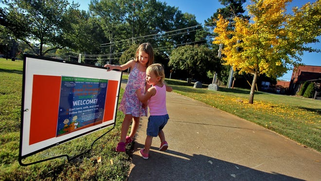"""Aubrey, and Remy Shook, 2, spend a fall afternoon reading """"It's The Great Pumpkin Charlie Brown"""" along a walk around Patriots Park in Kings Mountain."""