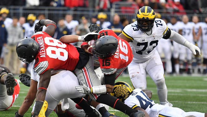 COLUMBUS, OH - NOVEMBER 26:   J.T. Barrett #16 of the Ohio State Buckeyes rushes for a first down during overtime of the game against the Michigan Wolverines at Ohio Stadium on November 26, 2016 in Columbus, Ohio.  (Photo by Jamie Sabau/Getty Images) ORG XMIT: 678475575 ORIG FILE ID: 625979532