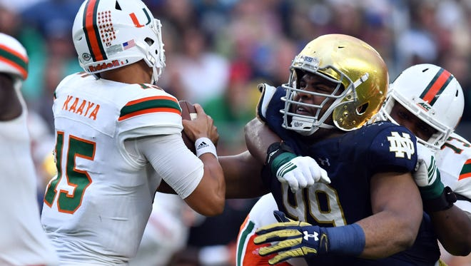 Oct 29, 2016; South Bend, IN, USA; Miami Hurricanes quarterback Brad Kaaya (15) is pressured by Notre Dame Fighting Irish defensive lineman Jerry Tillery (99) in the third quarter at Notre Dame Stadium. Notre Dame won 30-27. Mandatory Credit: Matt Cashore-USA TODAY Sports