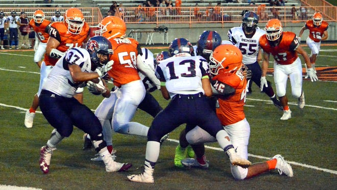 Deming's Trini Garcia (37) fights for extra yards in the first quarter Friday at Artesia.