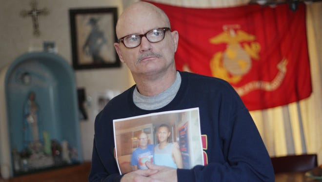 Tom Swann, a Marine Corps. veteran is photographed at his home in Rancho Mirage holding a photo of him and his fiance Guillermo Hernandez. Days after Swann proposed, immigration officers arrested Hernandez, who is undocumented. In March the two will become the first same-sex couple to marry inside a federal immigration facility in the U.S.