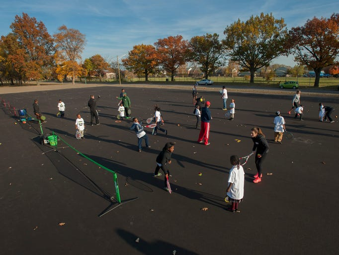 Children learn to play tennis during a ceremony for