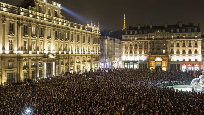 Thousands of people gather for a moment of silence to pay their respects to the victims of the deadly attack at the Paris offices of French satirical newspaper Charlie Hebdo, in Lyon, central France, Wednesday, Jan. 7, 2015. Masked gunmen stormed the Paris offices of a weekly newspaper that caricatured the Prophet Muhammad, killing at least 12 people, including the editor, before escaping in a car. It was France's deadliest postwar terrorist attack. (AP Photo/Laurent Cipriani)