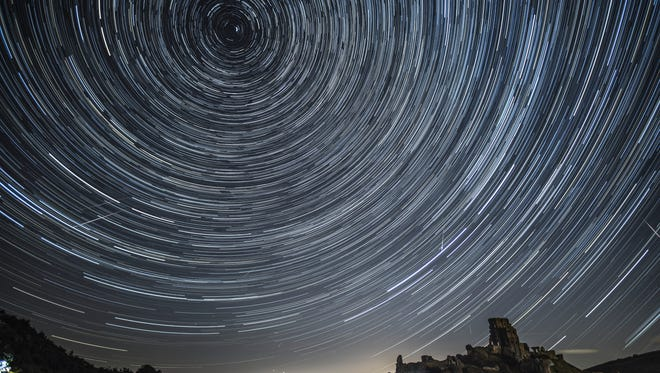 United Kingdom, composite image: Satellites, planes and comets transit across the night sky under stars that appear to rotate above Corfe Castle on August 12, 2016 in Corfe Castle, United Kingdom.