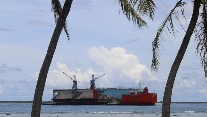"""After more than two decades on Guam, the """"Big Blue"""" dry dock — nicknamed for the color of its paint — is shipped out of Apra Harbor Tuesday, in two pieces. It was shipped out by the M/V Zhen Hua 28, out of Hong Kong. The drydock, owned by the Guam Shipyard, was damaged in early January 2011, when it took on water because of high surf."""