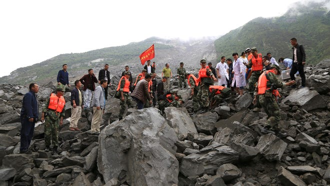 In this photo released by China's Xinhua News Agency, emergency personnel work at the site of a landslide in Xinmo village in Maoxian County in southwestern China's Sichuan Province, on June 24, 2017. More than 120 people were feared buried by a landslide that unleashed huge rocks and a mass of earth.