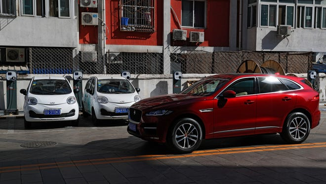 An SUV rolls past electric cars parked at a charging station outside a residential building in Beijing. Momentum is building worldwide for electric cars thanks to rising government fuel economy standards and climate concerns.