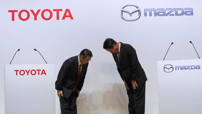 Toyota Motor Corp. President Akio Toyoda, left, and Mazda Motor Corp. President Masamichi Kogai, right, bow prior to a press conference this month in Tokyo. Japanese automakers Toyota and Mazda plan to spend $1.6 billion to set up a joint-venture auto manufacturing plant in the U.S. — a move that will create up to 4,000 jobs. (AP Photo/Eugene Hoshiko, File)