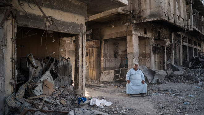 In this Nov. 18, 2017, photo, shop owner Abu Azar sits outside a destroyed bazaar in the Old City of Mosul, Iraq. The cost to rebuild after driving out the Islamic State group will be enormous. Baghdad estimates $100 billion is needed nationwide.