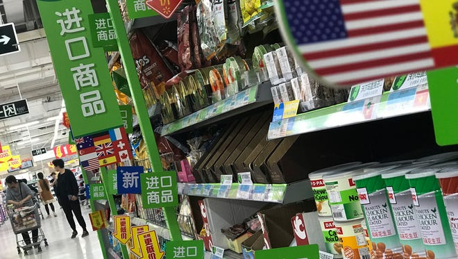 FILE - In this Monday, April 2, 2018, file photo, women push a shopping cart near nuts and sweets imported from the United States and other countries displayed on a section selling imported foods at a supermarket in Beijing. China's government has renewed its threat to scrap deals with Washington aimed at defusing a sprawling trade dispute as the White House prepares to release a list of Chinese goods targeted for tariff hikes. (AP Photo/Andy Wong, FIle) ORG XMIT: BKWS104