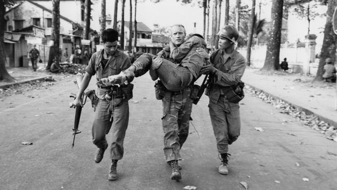 First Lt. Gary D. Jackson of Dayton, Ohio, carries a wounded South Vietnamese Ranger to an ambulance Feb. 6, 1968 after a brief but intense battle with the Viet Cong during the Tet Offensive near the National Sports Stadium in the Cholon section of Saigon. (AP Photo/Dang Van Phuoc)