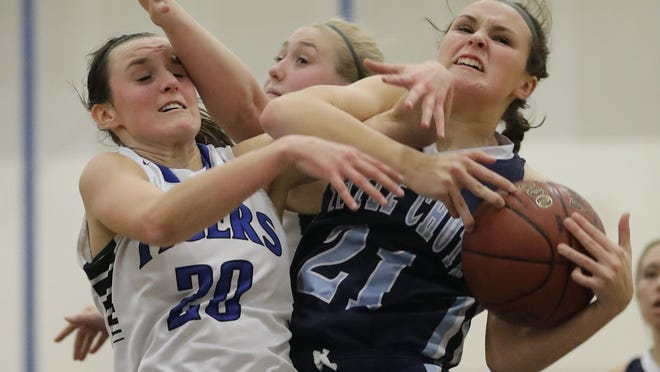 Little Chute's Kendra Schumacher (21) pulls down a rebound against Wrightstown's Danielle Nennig (20) and Alexis Wolske on Tuesday.