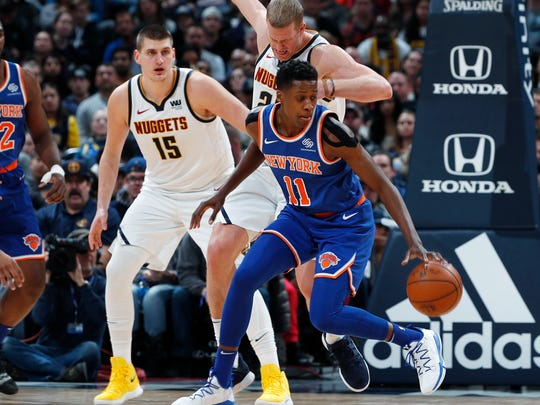 New York Knicks guard Frank Ntilikina, front right, gets control of the ball as Denver Nuggets center Nikola Jokic, left, and forward Mason Plumlee defend during the second half of an NBA basketball game Tuesday, Jan. 1, 2019, in Denver. The Nuggets won 115-108. (AP Photo/David Zalubowski)