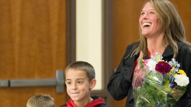 Terri Tchorzynski with her kids Dave, left and Broc during a surprise presentation for receiving the Nation's Counselor of the Year on Thursday.  Tchorzynski is a counselor at the Calhoun Area Career Center in Battle Creek.