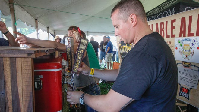 Founders Brewing's Casey Baxter, of Brighton, pours the brewery's iconic Kentucky Breakfast Stout (KBS) during a special tapping Friday at the Michigan Summer Beer Festival in Ypsilanti's Riverside Park.