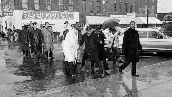 This March 1,1965 file photo shows Dr. Martin Luther Jr. hopping over a puddle as it rains in Selma, Ala. King led hundreds of African Americans to the court house in a voter registration drive. At front is civil rights worker Andrew Young, and at right, behind King is Rev. Ralph Abernathy. Today's protests across America against racial injustice are being watched closely by people who five decades ago faced jail cells, bloody assaults, snarling dogs and even potential assassination in the battle against institutional racism. The Associated Press interviewed veterans of the 1960s civil rights movement for their thoughts on then and now.