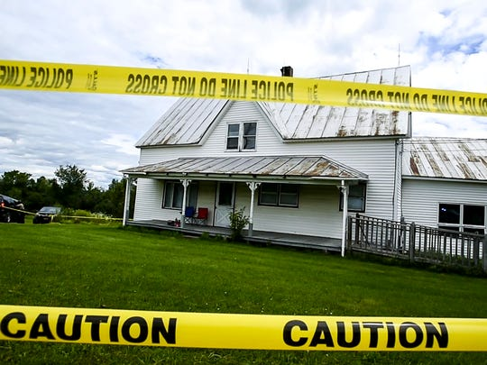 Police tape surrounds a house on Airport Road in Berlin where three family members were found shot to death on Saturday, August 8, 2015.