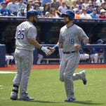Royals left fielder Ben Zobrist (18) is congratulated by designated hitter Kendrys Morales (25) after scoring a run during the sixth inning against the Toronto Blue Jays at Rogers Centre on Saturday.