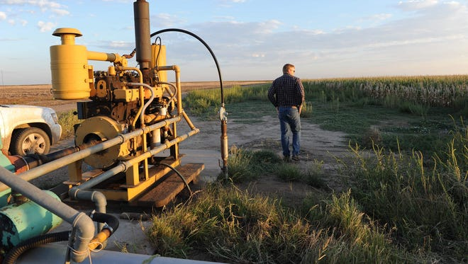 "Jay Garetson looks into a cornfield next to a pump on his family's farm in southwestern Kansas. A judge Tuesday, Jan. 31, 2017, ruled in favor of Garetson's lawsuit by concluding his family's senior water right had been ""impaired"" by their neighbor — a company that holds a junior water right."