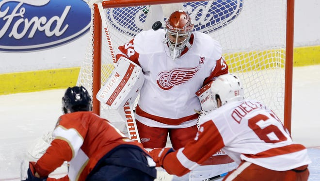Detroit Red Wings goalie Petr Mrazek (34) stops a shot by Florida Panthers defenseman Aaron Ekblad (5) as Red Wings' Xavier Ouellet (61) also defends during the third period.