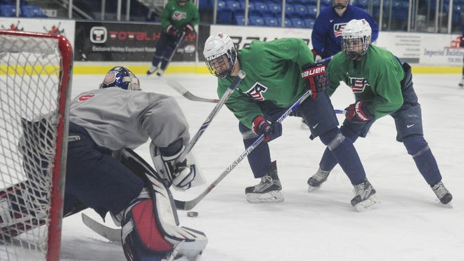 USA's Randy Hernandez and Jacob Tortora move in on goalie Dylan St. Cyr during practice last week at USA Hockey Arena in Plymouth.