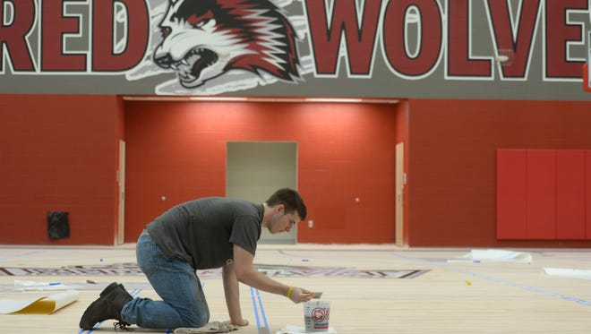 Chris Schlenker paints the gymnasium floor Friday, Aug. 5, 2016 of Indiana University East's new Student Activities and Events Center in Richmond.