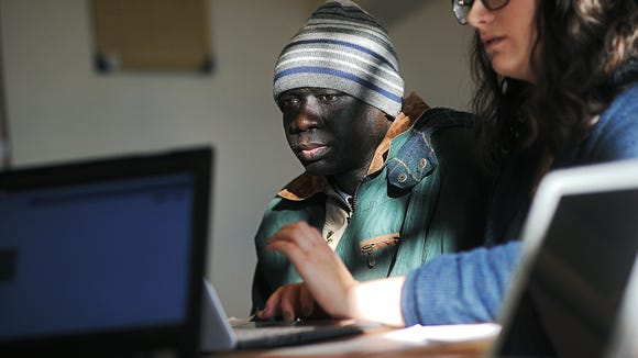 Paul Madut looks on as Tamara Meyerhoff, a job skills program recruiter, helps him with his resume and apply for jobs as part of the Multi-Cultural Center's job skills program Tuesday, Feb. 9, 2016, at the Multi-Cultural Center in downtown Sioux Falls.