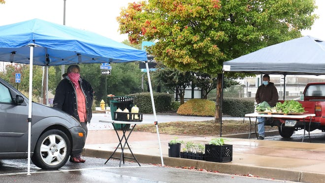 Martha Stilley, left, and Cordell Carr set up their vendor booth, Tuesday, Oct. 27, for the last Tuesday market day until April 2021 at the Downtown Farmers Market on Garrison Ave. The Saturday market is open 7 a.m. to noon through November and 8 a.m. to noon December 2020 through March 2021.